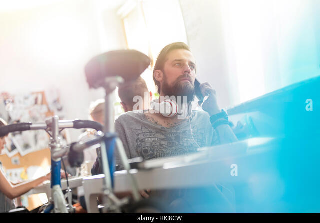 Bicycle leaning against desk next to serious male design professional with headphones talking on cell phone - Stock-Bilder
