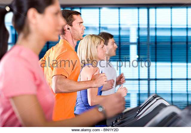 Men and women running on treadmills in health club - Stock Image
