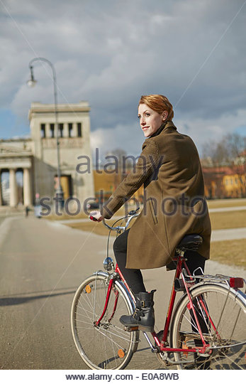 Woman cycling, monument in background, Munich, Germany - Stock Image