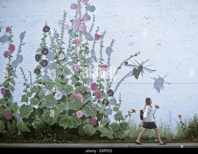 Woman walking by flowery wall - Stock Image