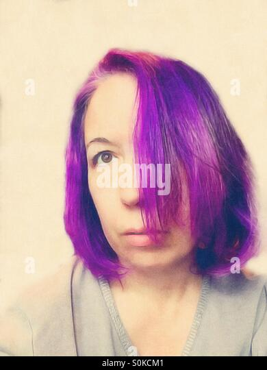 Woman with purple hair with one eye covered looking upward to the side - Stock Image