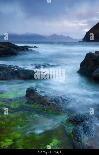 Looking towards the island of Kalsoy from the rocky shores of Gjogv, Eysturoy, Faroe Islands. Spring (June) 2012. - Stock Image