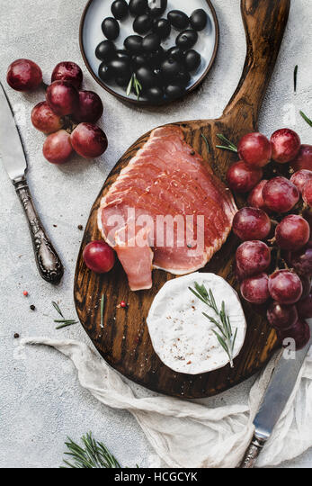 Assorted italian antipasti snacks for a dinner with wine or party on wooden cutting board. - Stock Image