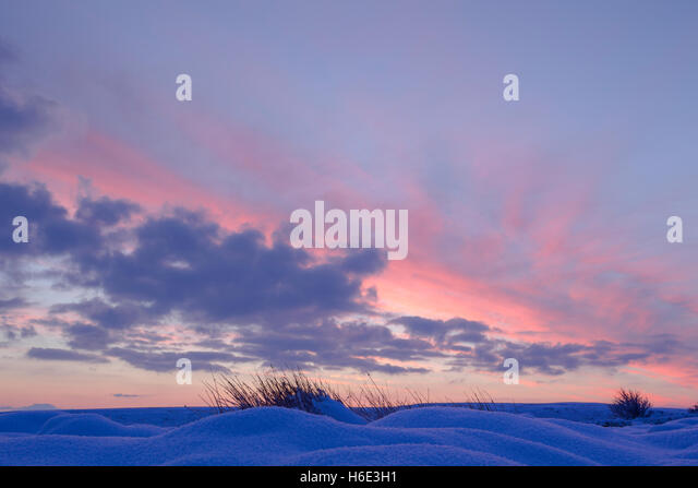 Colourful sky and clouds at daybreak over snow covered mounds in North York Moors national park - Stock Image