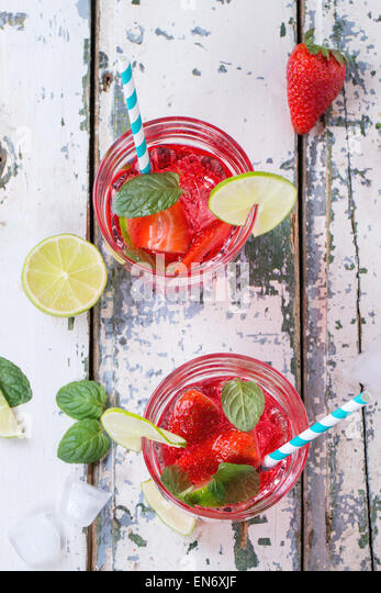 Two glasses with retro cocktail tubes and glass jug of homemade strawberry lemonade, served with fresh strawberries, - Stock Image