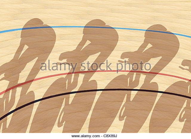 Cyclists casting shadows on indoor track - Stock Image