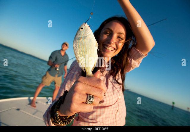 A woman smiles and holds up a small fish in Florida. - Stock-Bilder