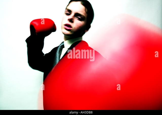Youth in Suit with boxing Gloves punching at camera - Stock Image