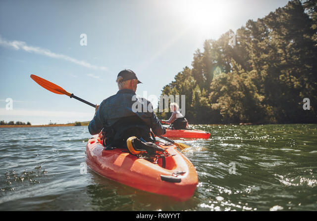 Outdoor shot of mature man canoeing in the lake with woman in background. Couple kayaking in the lake on a sunny - Stock-Bilder