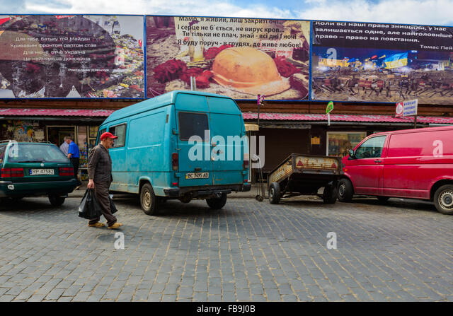 Man with plastic bag walking past cars and Maydan-themed billboards in a Lviv market, Ukraine - Stock Image