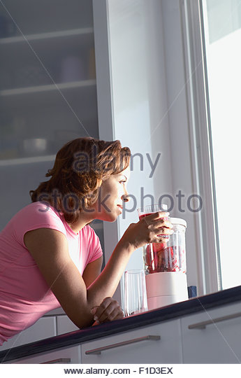 Woman drinking smoothie by kitchen window - Stock Image