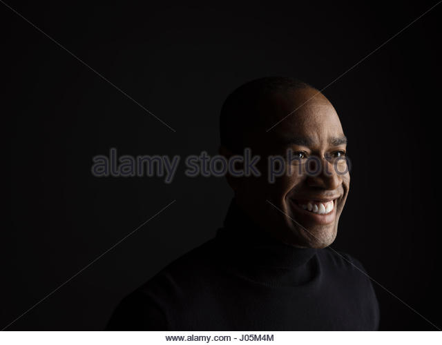 Portrait smiling African American man looking away against black background - Stock Image