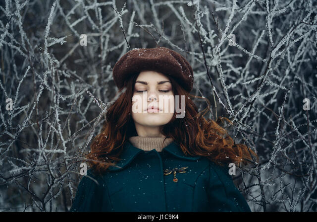 Caucasian woman with eyes closed near icy branches - Stock Image
