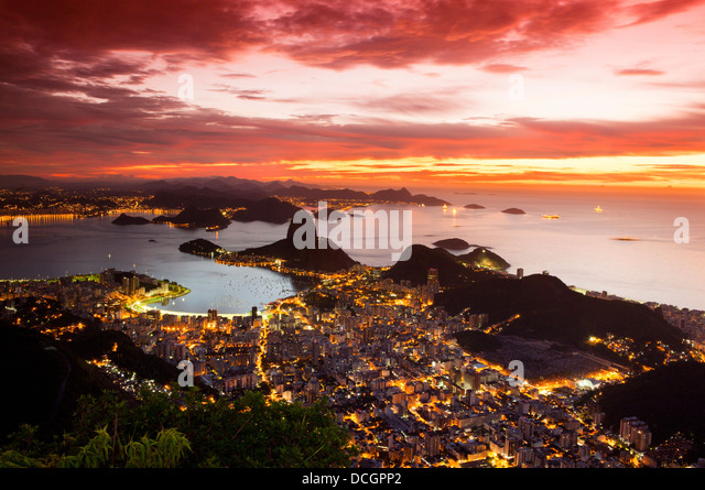 Rio de Janeiro cityscape, Brazil. Sugar Loaf, Botafogo beach and neighborhood seen from Corcovado at sunrise, red - Stock Image