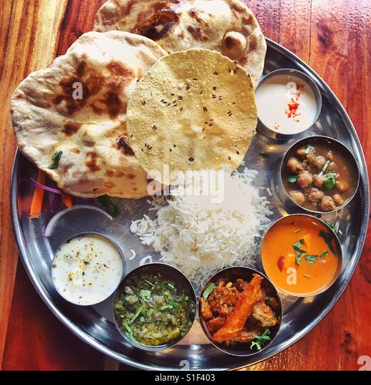 An Indian thali of assorted curry, naan bread, pappadum, rice at Maya, Surry Hills, Sydney - Stock Image