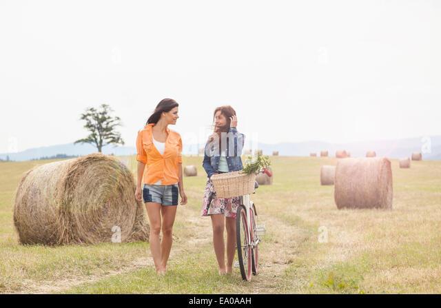 Friends with bicycle walking on field, Roznov, Czech Republic - Stock-Bilder