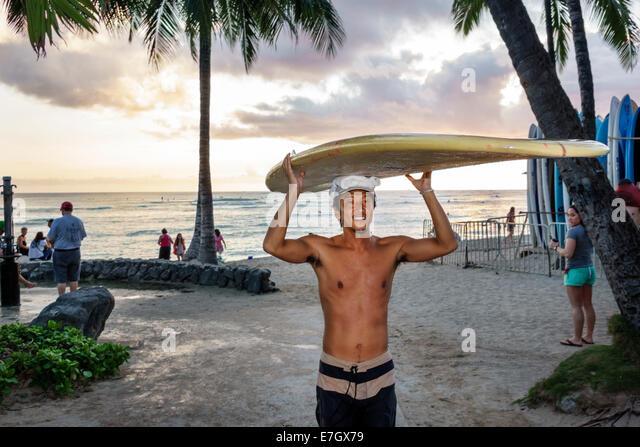 Waikiki Beach Honolulu Hawaii Hawaiian Oahu Kuhio Beach Park Pacific Ocean Waikiki Bay Asian man surfer surfboard - Stock Image