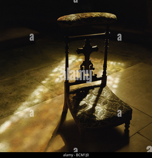 Church kneeler bathed in light coming through stained glass - Stock Image