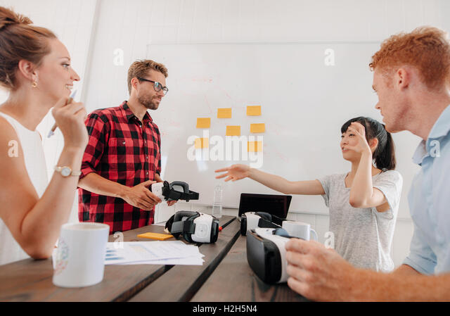 Shot of group of diverse business people discussing virtual reality technology in meeting room. Developers brainstorming - Stock Image