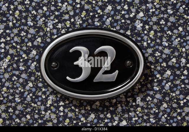 Number 32 metal silver and black house sign on a floral background. - Stock Image
