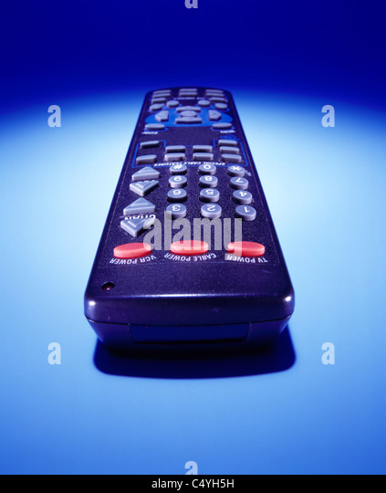 A television's VCR DVD or cable remote control device on a glowing blue background - Stock Image