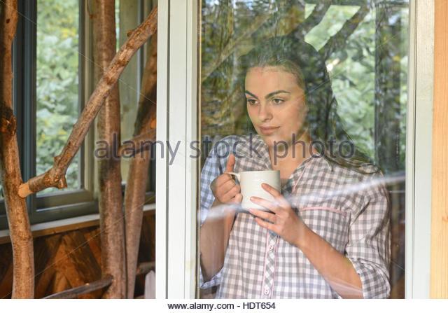 Young woman drinking coffee beside window. - Stock Image