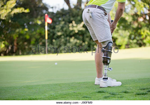 Male Golfer With Artificial Leg On Course Putting Ball On Green - Stock-Bilder