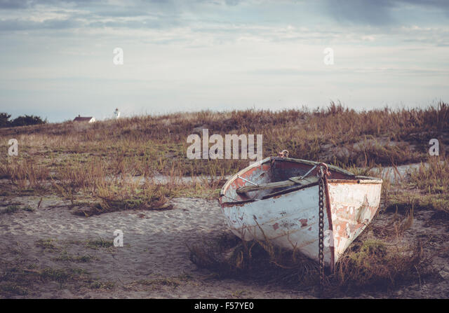Shipped small boat sitting on the beach at sunset. Old and weathered and abandoned. - Stock Image