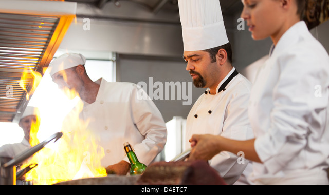 Chefs cooking in restaurant kitchen - Stock Image