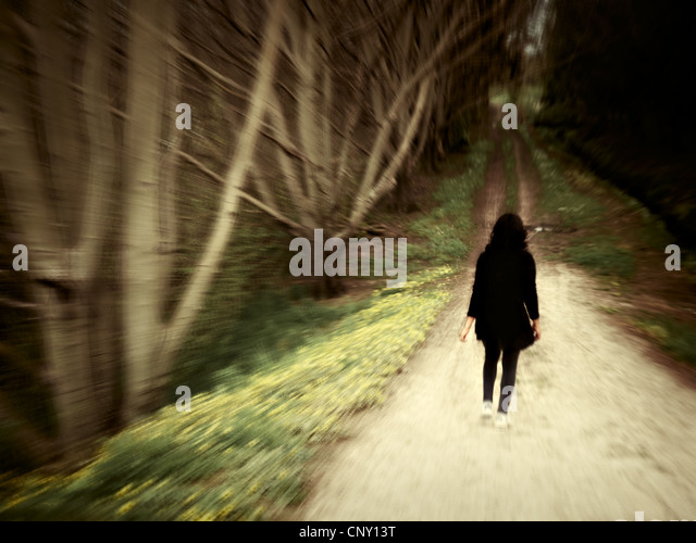 Woman walks along woodland track. - Stock Image