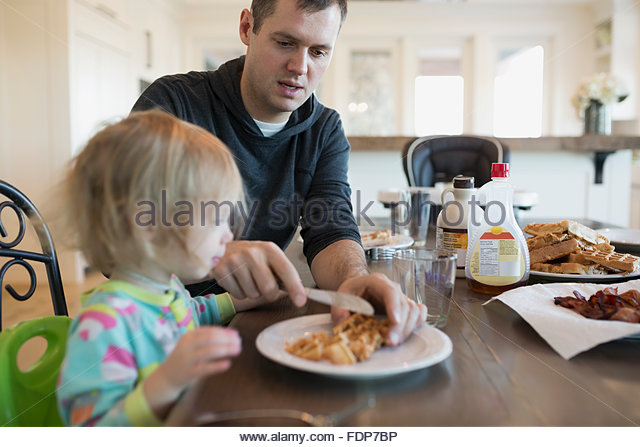 Father cutting waffles for daughter at breakfast table - Stock Image