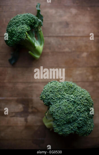 Broccoli florets on a rustic wooden cutting board - Stock Image