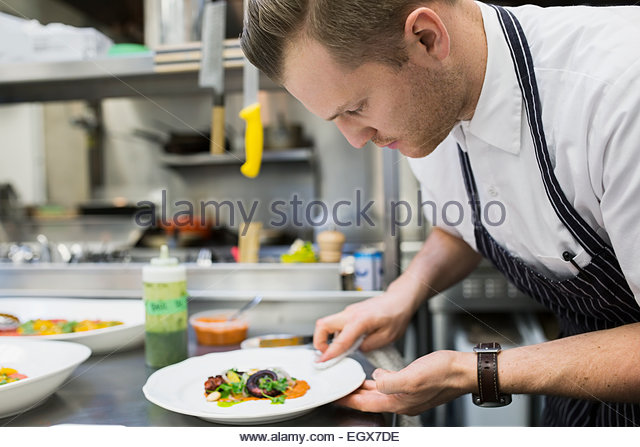 Chef wiping plate of food in commercial kitchen - Stock Image