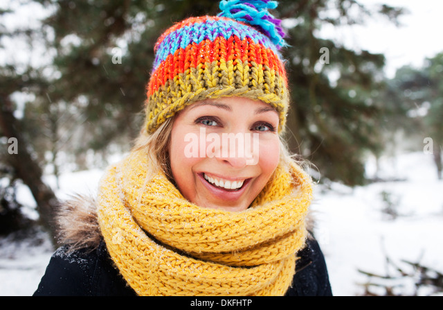 Close up portrait of woman in wooly hat and scarf in winter - Stock Image