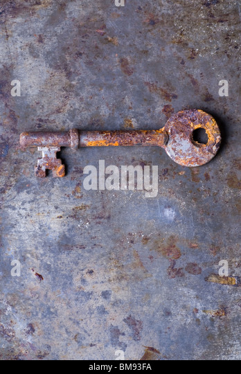 Dirty old rusted house key over a grunge background - Stock Image