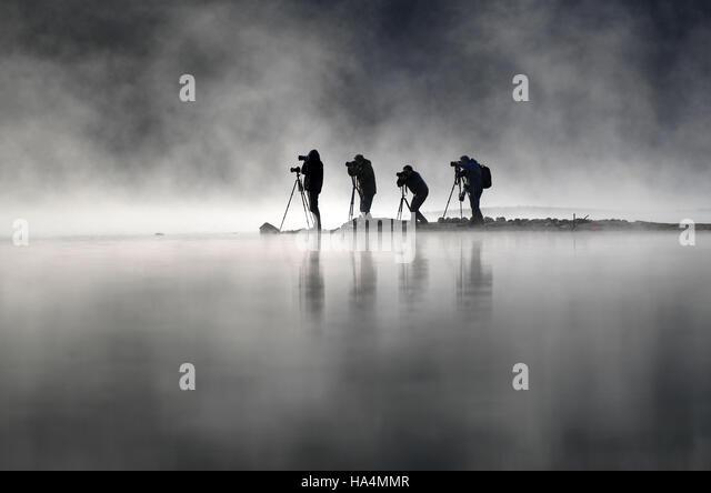 Yixian, China's Anhui Province. 28th Nov, 2016. Photographers take photos of fog-enveloped Qishu Lake in Yixian - Stock Image