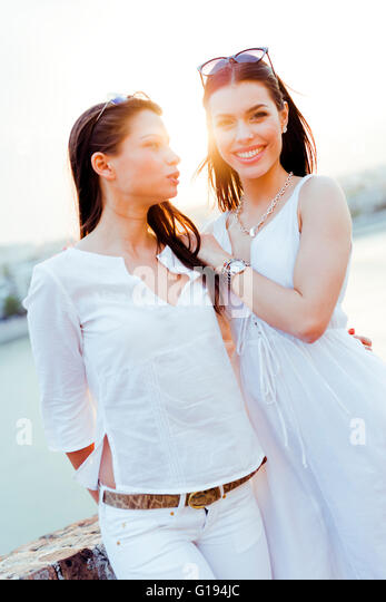 Young and beautiful women smiling and being happy while dressed in white - Stock Image