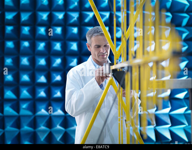 Scientist in lab coat preparing to measure electromagnetic waves in anechoic chamber - Stock-Bilder