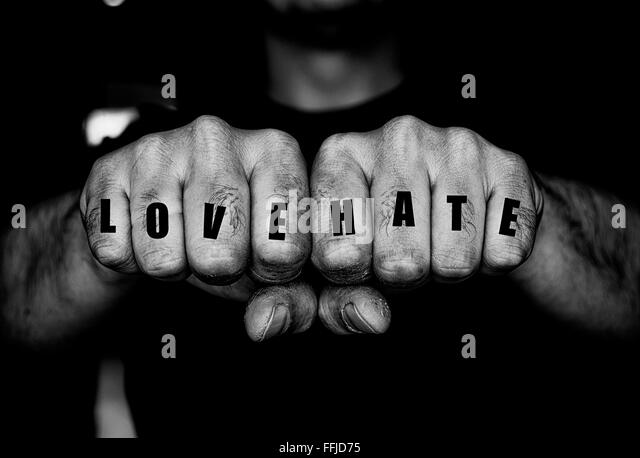 Thug's clenched fists with scars with fake Love and Hate tattoos on the fingers. Toned image with added grain - Stock Image