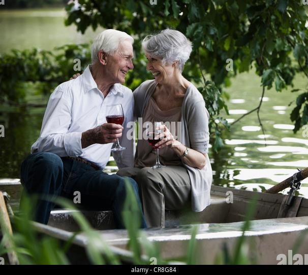 Senior couple drinking wine on rowing boat - Stock Image