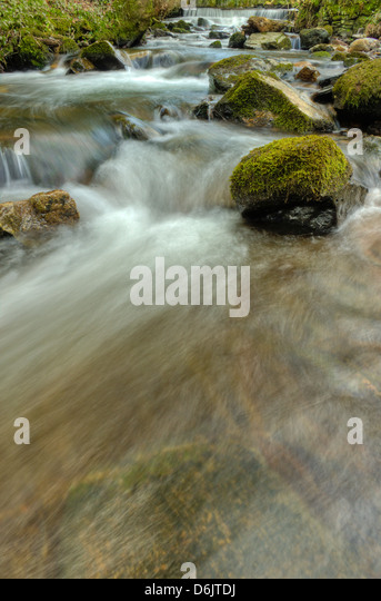 Dappled light upon the swift waters of the River Ashburn in Whiddon Scrubs on Dartmoor - Stock Image