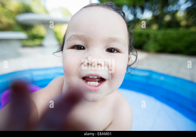 Close up candid portrait of a baby girl in paddling pool - Stock Image