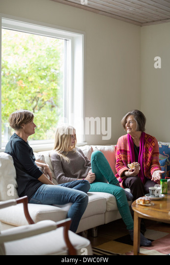 Three generation females spending leisure time in living room - Stock Image