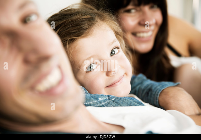 Young parents with little daughter sitting on sofa at home, close-up - Stock-Bilder