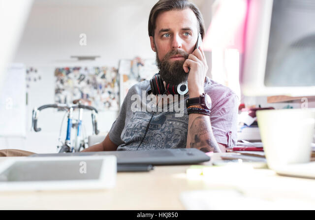 Pensive design professional with headphones talking on cell phone at desk - Stock-Bilder