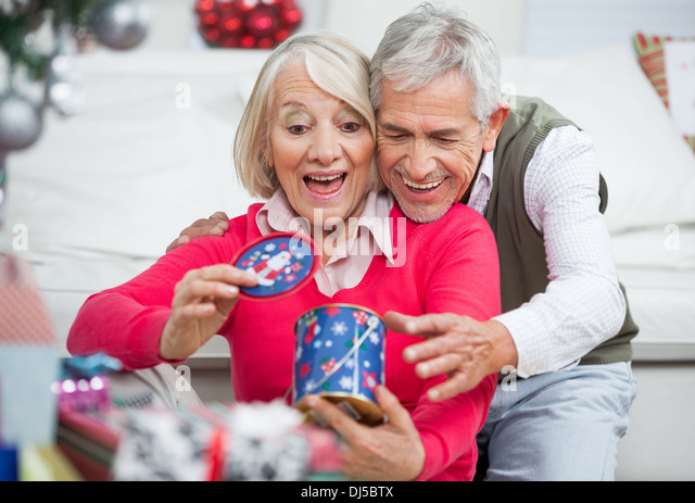 Surprised Senior Woman With Man Looking At Christmas Gift - Stock Image