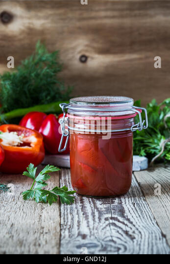 Homemade  pickled peppers in tomato juice and sweet bell red pepper on rustic table - Stock Image