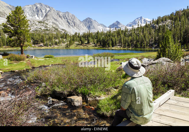 Resting hiker admires view in Little Lakes Valley in Rock Creek Canyon in the Eastern Sierra in Northern California - Stock-Bilder