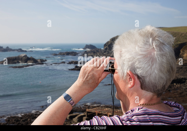 Senior woman looking through binoculars out to sea on coast at most southerly point on mainland Britain. Lizard - Stock Image