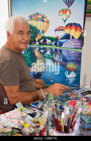 Older artist painting in studio - Stock Image
